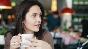 Girl drinking coffee and talking to someone. Girl drinking coffee laughing and talking  to someone in cafe stock video footage