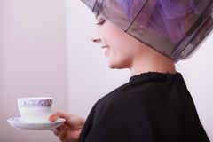 Girl drinking coffee tea by hairstylist. Hairdryer in hair beauty salon. Royalty Free Stock Photo