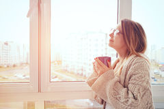 Girl drinking coffee or tea in morning Royalty Free Stock Images