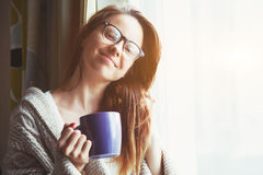 Girl drinking coffee or tea in morning sunlight Royalty Free Stock Photos