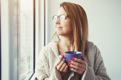 Girl drinking coffee or tea in morning sunlight Stock Images