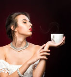 Girl drinking cup of hot coffee or tea Stock Images
