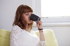 Girl drinking from a cup. A young beautiful woman is drinking a cup of coffee or tea relaxing on the couch Stock Photo