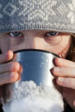 Girl drinking from flask cup. Closeup portrait of teenagergirl in winter hat drinking from flask cup Royalty Free Stock Photography