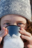Girl drinking from flask cup. Closeup portrait of teenagergirl in winter hat drinking from flask cup Stock Photos