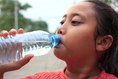 Girl drinking fresh water from bottle stock image