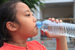 Girl drinking fresh water from plastic bottle Stock Photos