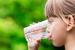 Girl drinking glass of fresh water. Close-up of young scandinavian child drinking fresh and pure tap water from glass with a blurred green background Royalty Free Stock Images