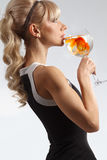 Girl drinking glass of water with golden fish Stock Photos