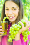 Girl drinking grapes juice outdoors Stock Photography