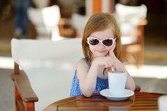 A girl drinking hot chocolate in outdoor cafe Stock Image