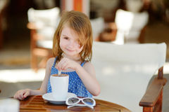 A girl drinking hot chocolate in outdoor cafe Stock Images