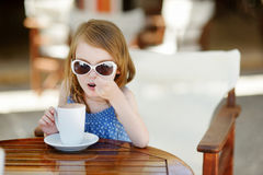 A girl drinking hot chocolate in outdoor cafe Royalty Free Stock Photo