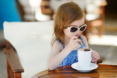 A girl drinking hot chocolate in outdoor cafe Royalty Free Stock Images