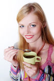 Girl drinking hot coffee or tea with spoon Stock Photos