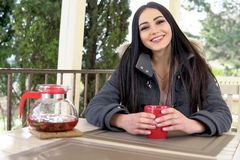 Girl drinking a hot drink in the outdoor restaurant Stock Photo