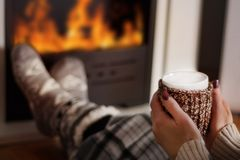 Girl drinking hot tea in front of the fireplace and warming legs stock photos