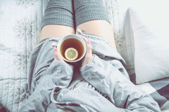 Girl is drinking hot tea on the sofa, cozy winter concept Royalty Free Stock Photos