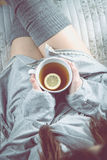 Girl is drinking hot tea on the sofa, cozy winter concept Stock Image