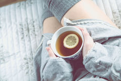 Girl is drinking hot tea on the sofa, cozy winter concept Royalty Free Stock Photo