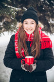 Girl drinking hot tea in the winter forest Stock Photo