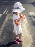 Girl drinking juice during crossing the street. Side view of girl drinking juice during crossing the street Stock Image