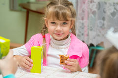 The girl is drinking juice and eating cookies at desk in the kindergarten Stock Photography
