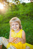 Girl drinking juice from a glass on the lawn Stock Images