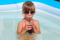 Girl drinking juice in the pool. Stock Photography
