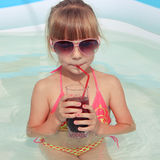 Girl drinking juice in  pool. Toned image Stock Photo
