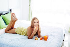 Girl drinking juice and relaxing in bedroom. 10 years old pre teen girl drinking orange juice while relaxing in bedroom. Healthy food for breakfast Royalty Free Stock Images