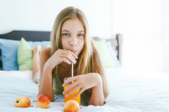 Girl drinking juice and relaxing in bedroom Stock Images