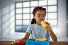 Composite image of girl drinking juice at table Royalty Free Stock Photo