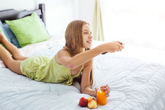 Girl drinking juice and watching tv in bedroom Royalty Free Stock Photo