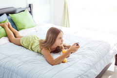 Girl drinking juice and watching tv in bedroom Royalty Free Stock Photos