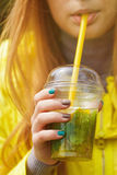 Girl is drinking a large glass of lemonade Stock Images