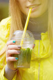 Girl is drinking a large glass of lemonade Royalty Free Stock Image