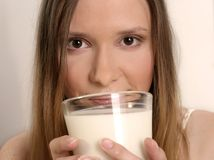 Girl drinking milk. Young blond woman, girl drinking milk from a glass Stock Image