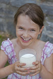 Girl is drinking milk. Seven year old girl is drinking milk outside in the summer Royalty Free Stock Photography