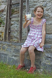 Girl is drinking milk. Seven year old girl is drinking milk outside in the summer Stock Image