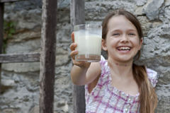 Girl is drinking milk. Seven year old girl is drinking milk outside in the summer Stock Photography