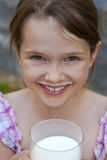 Girl is drinking milk. Seven year old girl is drinking milk outside in the summer Royalty Free Stock Photos