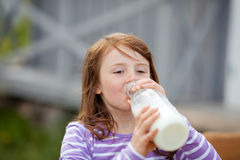 Girl Drinking Milk From Bottle At Campsite Stock Image