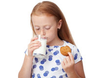 Girl drinking milk and eating a cookie Royalty Free Stock Photos