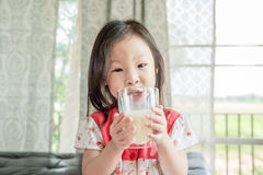 Girl drinking milk from glass Stock Photo