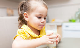 Girl drinking milk at the kitchen Stock Photography