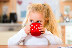Girl drinking milk in kitchen Stock Image