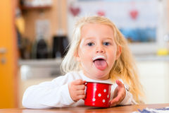Girl drinking milk in kitchen Stock Images