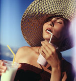 Girl drinking milk shakes. Beautiful girl wearing straw hat on the beach. She's drinking milk shakes. Film scan, middle format, flares Stock Photos