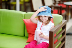 A girl drinking milkshake in outdoor restaurant Stock Photo
